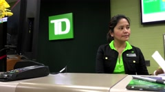 Woman holding US cheque to deposit for customer inside TD Bank Stock Footage