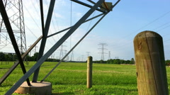 dolly across a power Transmission Tower in the middle of a large field 4k - stock footage