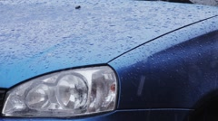Water droplets form on blue car body. - stock footage