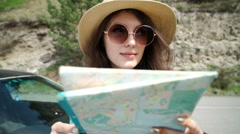 Travel - young woman with car look at road map on a beach against sea and sky Stock Footage