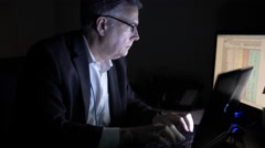 Businessman working at night using a laptop in his office 4k Stock Footage