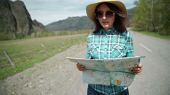 Happy young woman holding map on road Stock Footage