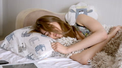 Cute girl sleeping in bed waking up and start using smartphone immediately Stock Footage