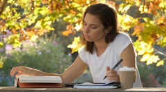 Warm autumn afternoon international student girl studying for exams essay test Stock Footage