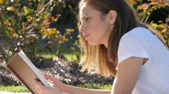 Bookish uni student girl reading a novel book outdoors on college campus Stock Footage
