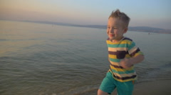Happy boy running on the sea coast at sunset - stock footage