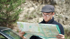 Young man reading a road map Stock Footage