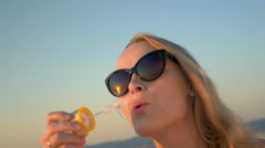 Young Woman in Sunglasses Blowing Soap Bubbles Stock Footage