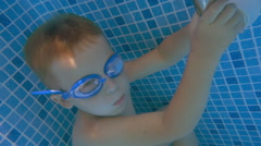 Boy in Goggles Holding Breath in Swimming Pool Stock Footage