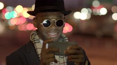 Young black man in bad boy look using smart phone in the city at night Stock Footage