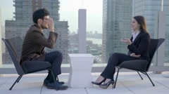 Two people sitting on rooftop building in the city talking together  Stock Footage