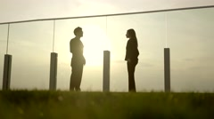 Silhouette view of man talking to women on rooftop lounge Stock Footage