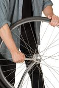 Man repairing front wheel on a bicycle - stock photo