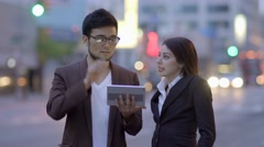 Young business people using tablet computer in the city at night Stock Footage