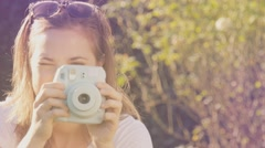 Portrait of hipster girl holding retor insta polaroid camera taking photo Stock Footage