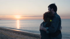 Happy loving couple on beach during sunrise or sunset, 4k Stock Footage
