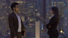Two young business people standing on rooftop building at night  Stock Footage