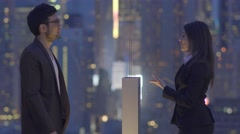 Small talk conversation of two young business people on rooftop at night Stock Footage