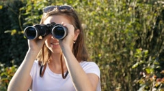 Millennial woman with binoculars searching looking into the future of her life Stock Footage
