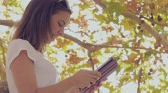 Student graduate studying on tablet pc wireless technology in autumn tree Stock Footage