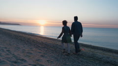 Happy loving couple walking on beach during sunrise or sunset, 4k Stock Footage