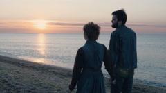 happy loving couple walking on beach during sunrise or sunset, 4k - stock footage