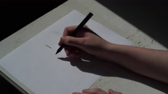 4K Woman writing I HATE YOU in black felt pen on white paper, adding fuck off Stock Footage