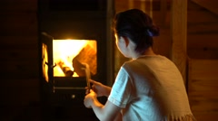 Woman  keeping the fire burning in the fireplace - stock footage