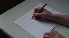 4K teenage girl is writing OMG! You're gorgeous on white paper on wooden table Stock Footage