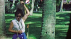 1964: Drunk mature woman puts big  coconut on head drops in on ground. Stock Footage
