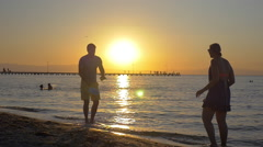 Couple Playing Racket Ball at Sunset - stock footage