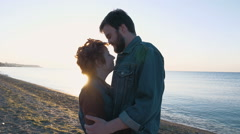 happy loving couple hugging on beach in sun beams, slow motion - stock footage