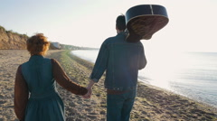 Happy loving couple walking on beach during sunrise or sunset with guitar Stock Footage