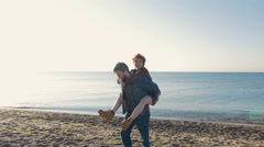 Happy loving couple having fun on beach during sunrise or sunset, slow motion Stock Footage