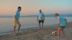 Men and Boy Playing Football on the Beach Stock Footage