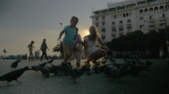 Boy Running among Pigeons during the Walk with Family Stock Footage