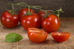 Cut in half cherry tomato with basil leaf - stock photo