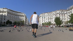 Young Man Making Vault on the Square with Pigeons Stock Footage