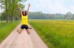 Energetic agile young woman leaping for joy Stock Photos