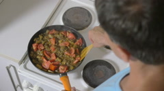 Man stewing tomatoes, mushrooms and potatoes in pan Stock Footage