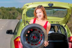 portrait of a beautiful girl holding a spare wheel of a car - stock photo