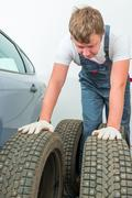 Mechanic inspects the automobile tires before installation Stock Photos