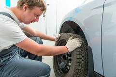 mechanic installs on the car winter tires in garage - stock photo