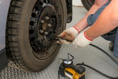 mechanic pump inflates the the wheel in garage - stock photo