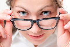 Very attentive girl watching glasses having lowered Stock Photos