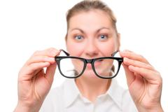 woman with poor eyesight wears glasses, focus on glasses - stock photo