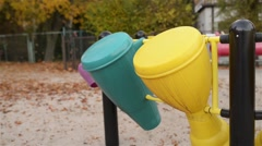 Little girl knocking on toy drum on playground - stock footage