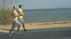 People in Headphones Jogging along the Esplanade Stock Footage