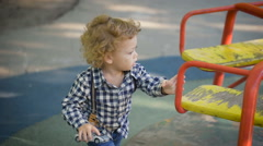 Happy little boy playing on the playground. He is very cute and naive Stock Footage