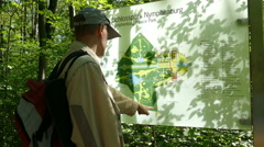 Tourist Man pointing finger to a park map Stock Footage